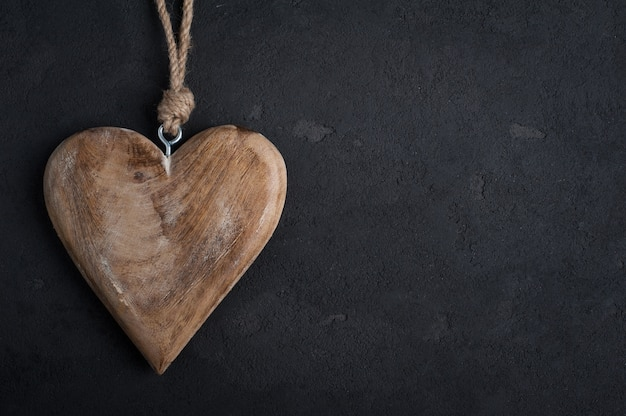 Concrete background with wooden heart with copyspace
