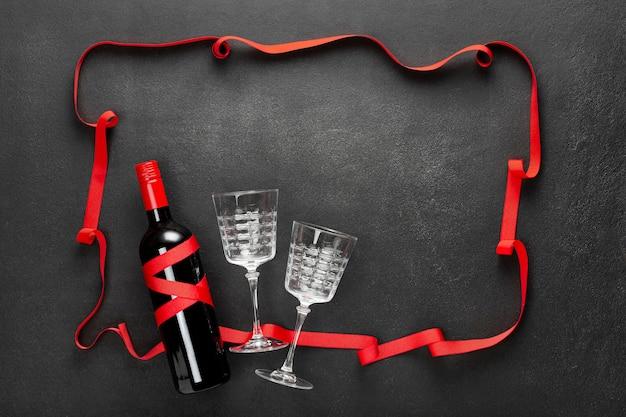 赤いリボン、赤ワインのボトル、ギフトボックスとコンクリートの黒の背景。休日の概念、お祝い、日付。