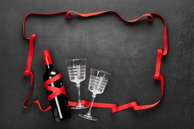 Concrete black background with a red ribbon, a bottle of red wine, and a gift box. holiday concept, congratulation, date.