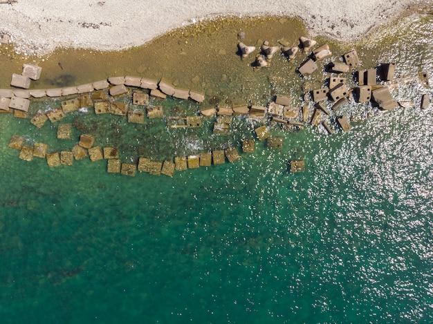 Бетонные блоки и четвероногие на берегу бирюзового моря. вид сверху, сделанный дроном