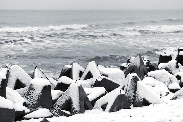Бетонные волноломы, покрытые снегом на фоне зимнего моря. береговая защита в снегу. снежный пасмурный пейзаж.