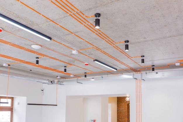 주황색 전기 배선 및 램프가 있는 콘크리트 천장