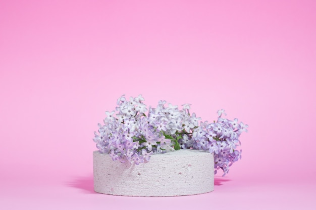 Concrete cylindrical podium with lilac flowers on a pink background with hard shadows. minimal empty cosmetic product presentation scene. geometric podium.