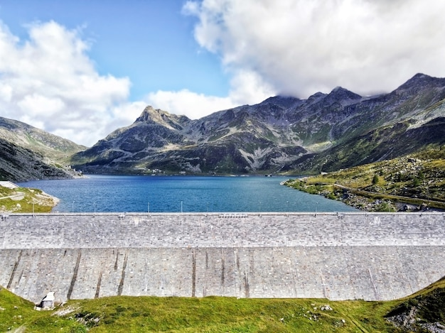 Concrete dam and water reservoir surrounded by mountains with green slopes under blue cloudy sky in summer day