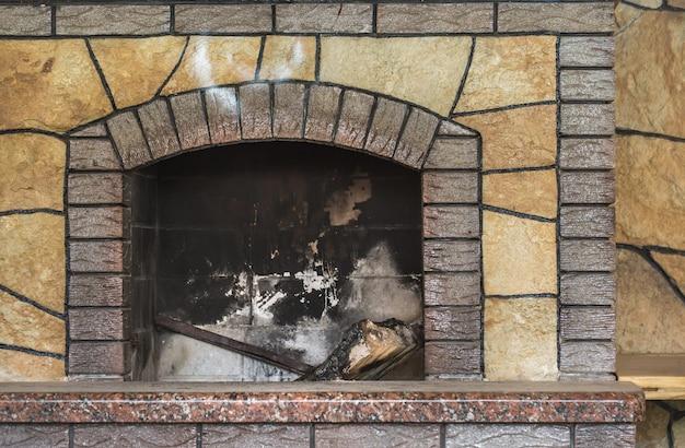 Бетонный грязный камин с остатками золы после сжигания деревянных дров в камине