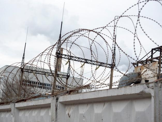 상단에 철조망이 있는 콘크리트 울타리. 침입으로부터 보호되는 폐쇄된 영역