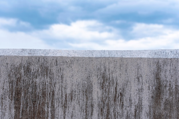 Concrete gray wall as border and blue sky as background
