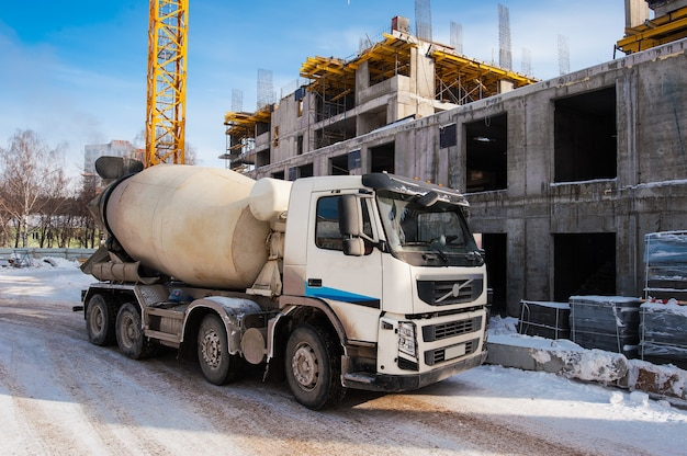 冬の建設現場にコンクリートミキサー車が立つ