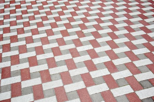 Бетонная или вымощенная недавно уложенная серо-красная тротуарная плитка или камень для полов или дорожек. бетонная тротуарная плитка во дворе или мощение дороги. садовая кирпичная дорожка во дворе на песчаном фундаменте.