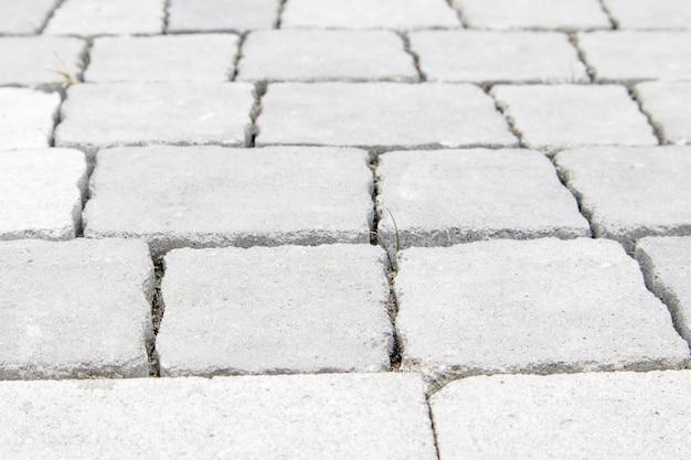 Бетонная или вымощенная недавно уложенная серая тротуарная плитка или камень для полов или дорожек. бетонная тротуарная плитка во дворе или мощение дороги. садовая кирпичная дорожка во дворе на песчаном фундаменте.