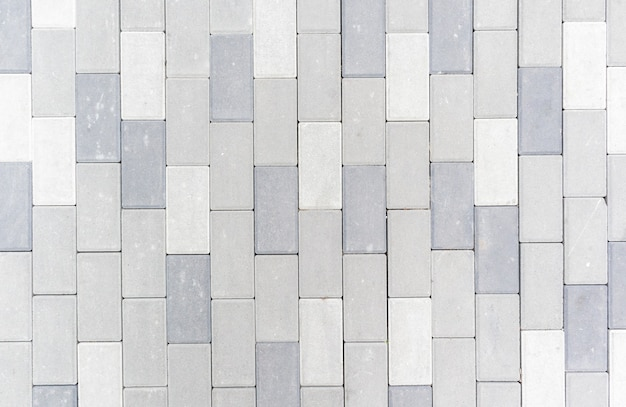 Concrete or paved newly laid gray paving slabs or stones for floors or walkways. concrete paving slabs in the backyard or road paving. garden brick path in the courtyard on a sandy foundation.