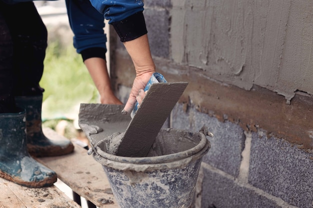 석고 도구로 산업 노동자 배경 벽을 만드는 콘크리트 미장.