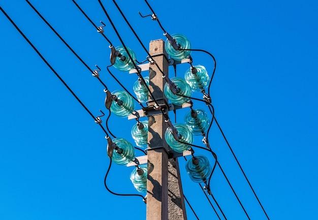 푸른 하늘을 배경으로 한 전송선의 일부로 전선과 고전압 분배 절연체가 있는 콘크리트 기둥.