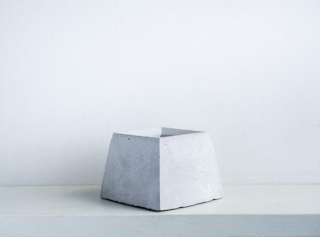 Concrete pot. empty modern geometric cement planter on white wood shelf on white