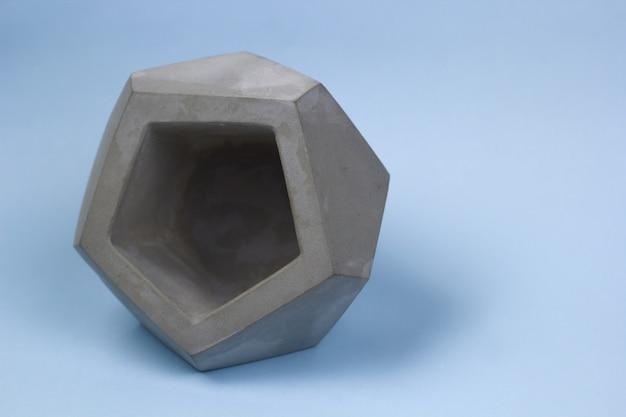 Concrete pot for plants, empty, polygonal shape, bright background