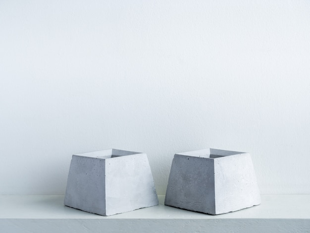 Concrete pot. two empty modern geometric cement planters on white wood shelf on white