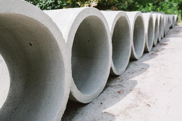 Бетонные кольцевые колодцы разного диаметра и серого цвета лежат на улице