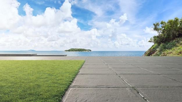 Бетонное дорожное покрытие и большой сад с видом на море. 3d иллюстрация пустой зеленой лужайки.