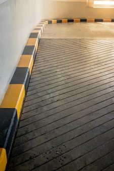 Concrete road and ramp with yellow and black curb in building