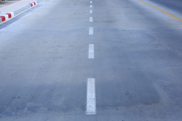 Concrete road with a white markings lane.