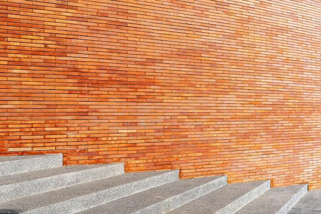 コンクリート階段と空きスペースのある赤い壁。抽象的な背景。建築および建設の背景。
