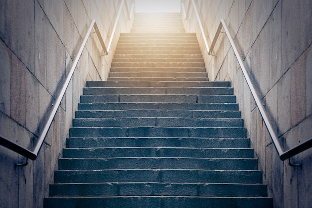 빛을 향해 이어지는 콘크리트 계단. 희망과 밝은 미래의 개념.