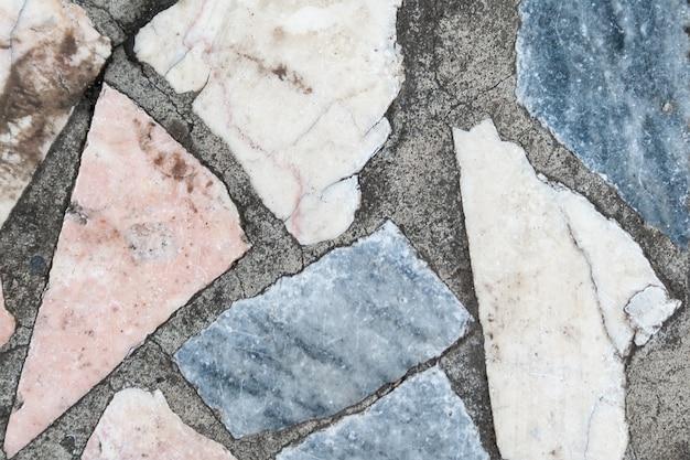 大きな色の石の複数のパッチがあるコンクリートの表面。閉じる