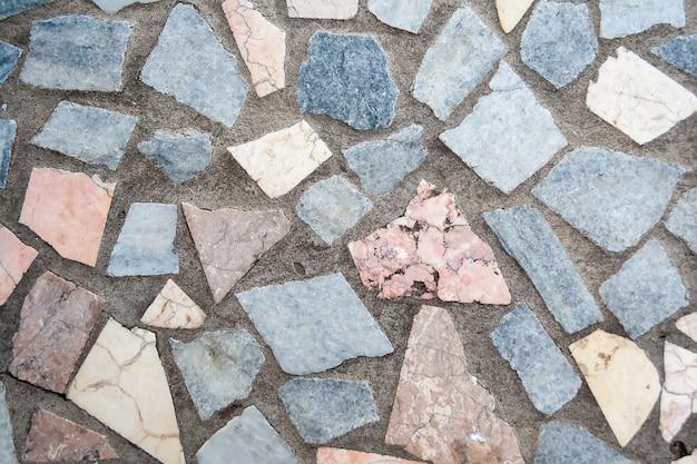 大きな色の石の複数のパッチがあるコンクリート表面
