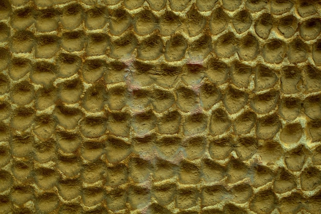 Concrete wall abstract honeycomb pattern and texture with dull dingy paint in a full frame view.