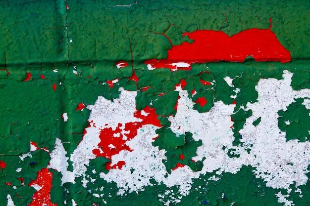 Бетонная стена, выкрашенная в зеленый, белый и красный цвета, отслаивающаяся от времени