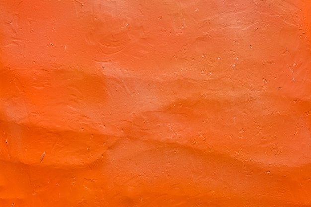 Бетонная стена окрашена оранжевой краской, фактурная.