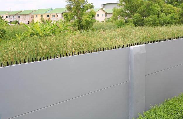 緑のフィールドの背景に黒の鋭い鉄の棒とコンクリートの壁。囲まれたフレームワークヘッジバーセクション。透視図