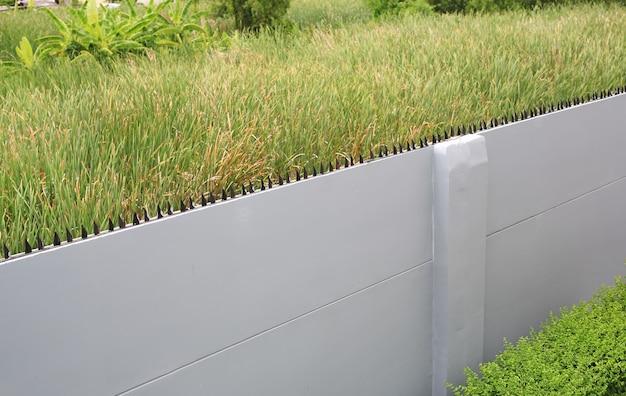 緑のフィールドの背景に黒の鋭い鉄の棒とコンクリートの壁