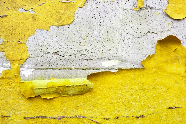 Бетонная стена с канареечно-желтой, оранжевой облупленной краской, старая треснувшая поврежденная грубая яркая текстура фона