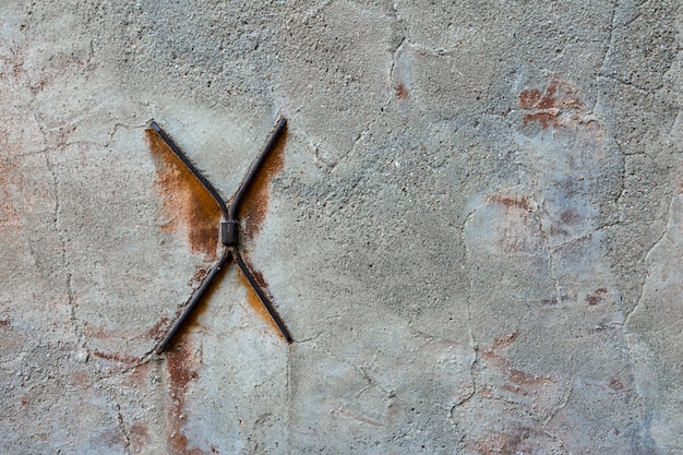 Concrete wall with cracks and metal brackets in the form of a cross.