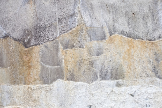 Concrete wall with divorces in the form of stripes of yellow and white. interesting background.