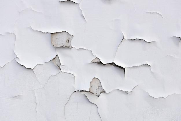 白いひびの入ったペンキが付いているコンクリートの壁。高品質の写真