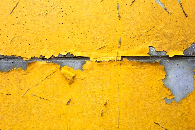 Concrete wall with yellow, orange peeling paint old cracked damaged rough bright background texture