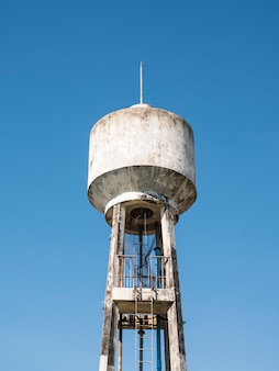 Concrete water tower with the metal ladder.