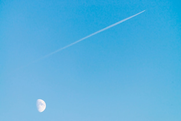 Condensation track of jet above moon in clear blue day sky. minimalist blue background. plane flies up diagonally.