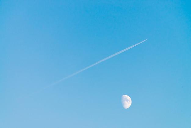 澄んだ青い空に月の上のジェットの凝縮トラック。シンプルな青い背景。飛行機は斜めに飛びます。飛行機は空域を飛んでいます。シアンの空に白い月。