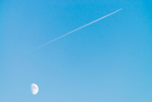 맑고 푸른 날 하늘에 달 위의 제트의 응축 트랙. 미니멀리스트 파란색 배경입니다. 비행기가 대각선으로 날아갑니다.
