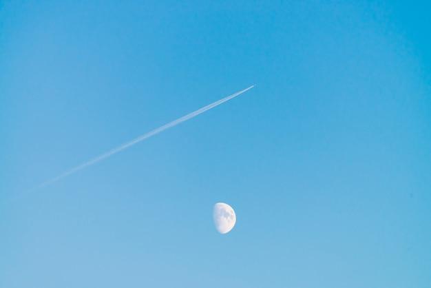 澄んだ青い空に月の上のジェットの凝縮トラック。飛行機は斜めに飛びます。飛行機は空域を飛んでいます。シアンの空に白い月。