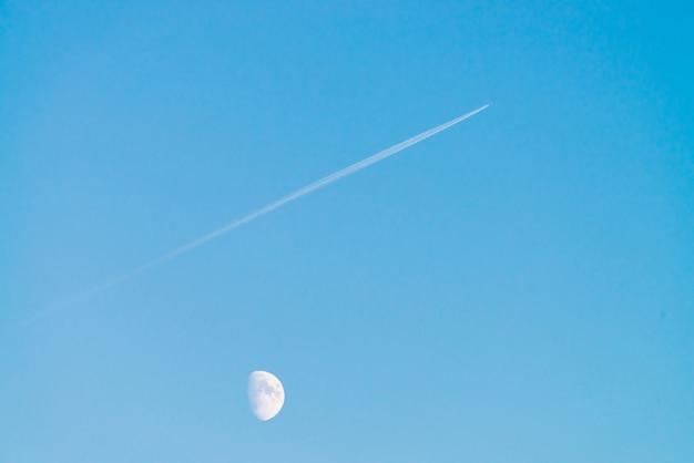 澄んだ青い日の空の月の上のジェットの凝縮トラック