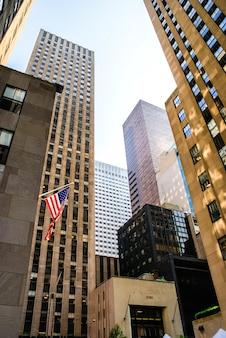 Сжатые и тесные американские небоскребы с американским флагом, прикрепленным к фасаду.