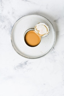 가벼운 콘크리트 테이블에 열린 통에 있는 농축 또는 증발 우유. 평면도.