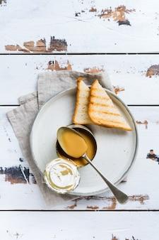 가벼운 오래 된 나무 테이블에 열린 주석에 농축 또는 증발 우유. 평면도.