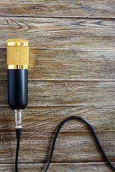 ケーブル付きのコンデンサーゴールドマイクは、コピースペースのある木製のテーブルの上にあります。音楽のテーマ。フラットレイ。上面図。