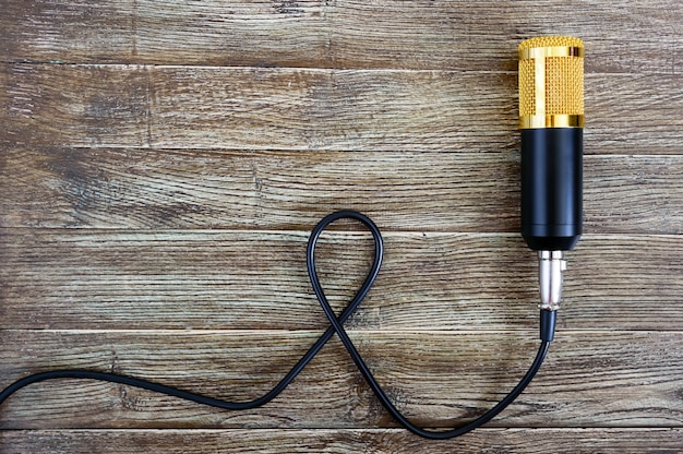 Condenser gold microphone with cable lies on a wooden table with copy space. musical theme. flat lay. top view.