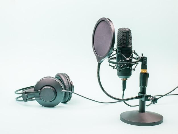 Конденсаторный микрофон и проводные наушники на синем фоне. оборудование для записи и воспроизведения звука.